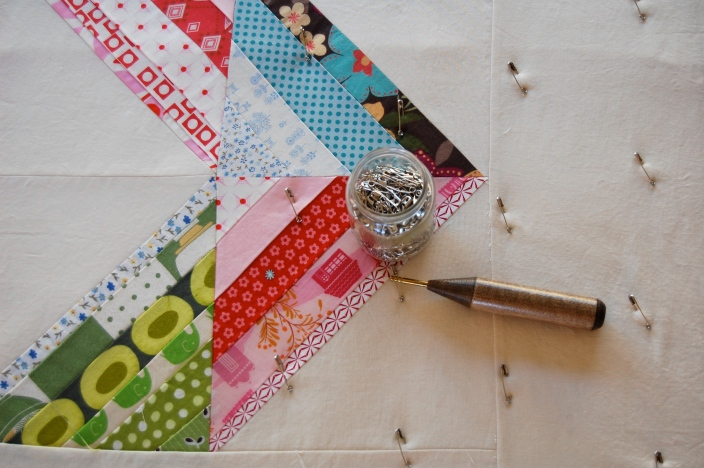 Miss A's scrappy HST quilt during basting