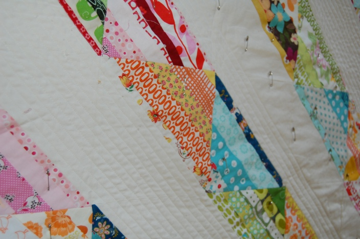 basting pins in scrappy strings quilt
